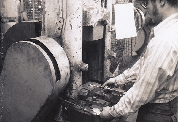 An Irwin employee at work using a coining machine, 1972