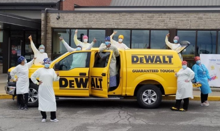 medical personnel standing in front of a yellow dewalt truck while wearing masks