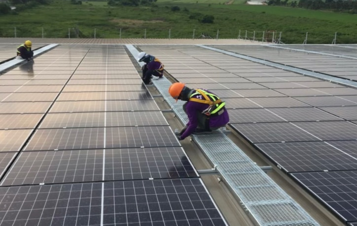 three people installing solar panels on a roof